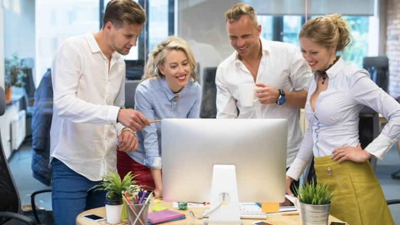 Group of creative agency workers looking at computer  in office