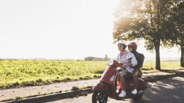 Junge und Maedchen fahren zusammen Moped