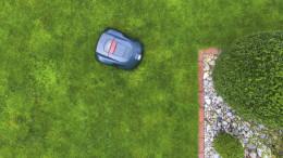 Ein Maehroboter liegt im Garten