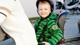 Ein kleiner Junge sitzt im Kindersitz auf einem Fahrrad
