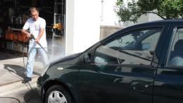 Mann waescht Auto in der Einfahrt