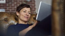 Eine Frau liegt auf dem Sofa und surft auf ihrem Tablet